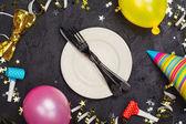 Világos ünnepi karnevál táblázatot, amely a lemez és a fekete kő asztal evőeszköz díszített party kellékek