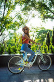 Young beautiful woman riding on bicycle in summer park. Green trees background