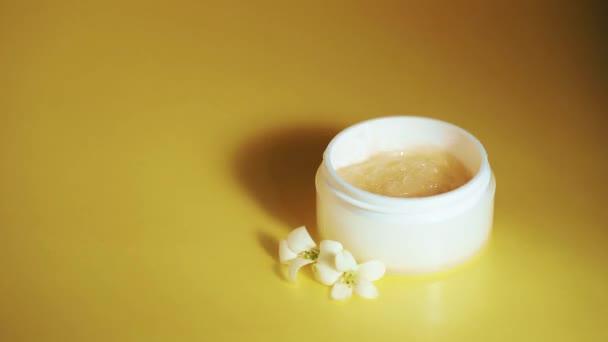 Kozmetikai háttér a termék bemutatásához. Gél krém fehér üvegben jázmin virágokkal sárga alapon. A pálmalevél mozgó árnyéka.