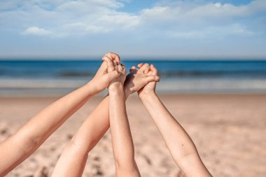 Close up picture of two little girls hands holding together laying on the sandy ocean beach.