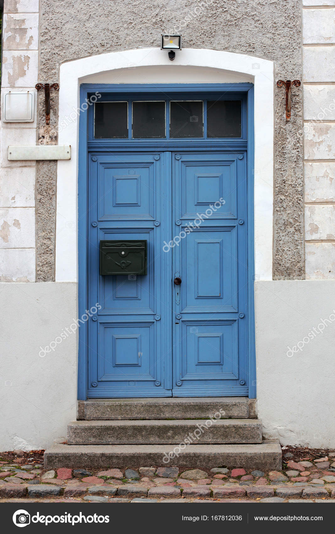 Closed blue door with the mailbox in a stone house Stock Photo