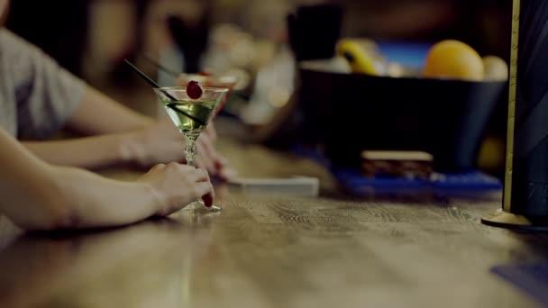 zwei Martini-Gläser mit Womens Händen neben