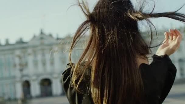 Krásná mladá žena pózuje a dotýká její vlasy