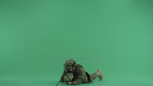 Soldier lying and targeting at the camera at green screen