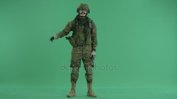 Soldier holding invisible bomb at green screen