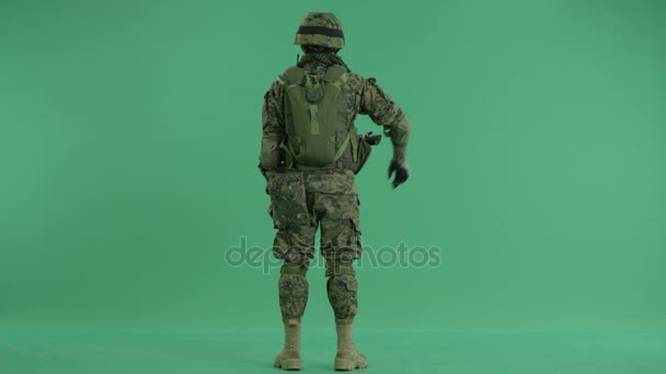 Soldier moving hands standing back at green screen