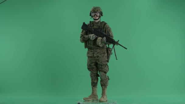 armed serviceman standing and rounding at green screen