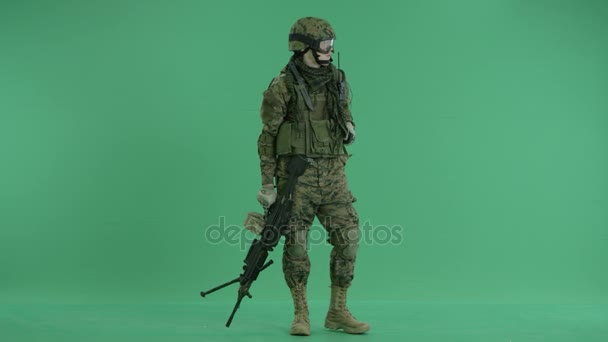 Soldier using gas mask and looking around at green screen