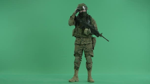 Soldier standing and targeting at camera at green screen
