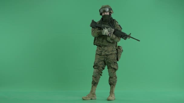 serviceman standing with weapon and looking at camera at green screen