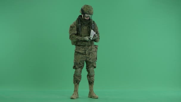 Soldier holding and counting money at green screen
