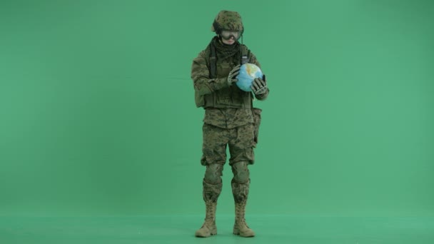 Soldier holding globus at green screen