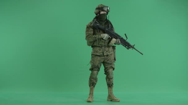 serviceman standing with weapon and looking at side at green screen