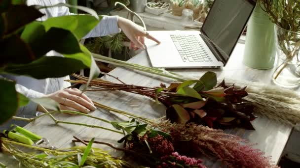 florist working with laptop and composing bouqet