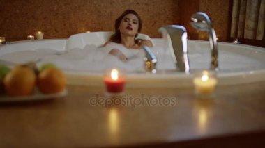 beautiful woman with cosmetics taking bath with foam
