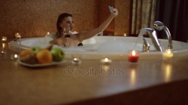 woman with red wine in bath with foam taking selfie