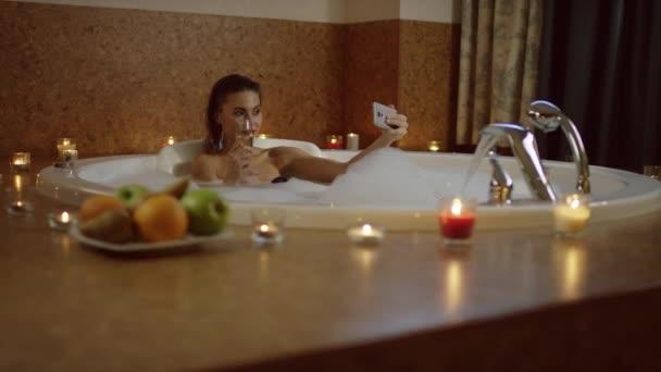 woman with cosmetics in bath with foam taking selfie