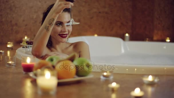 close ups of beautiful woman drinking red wine in bath