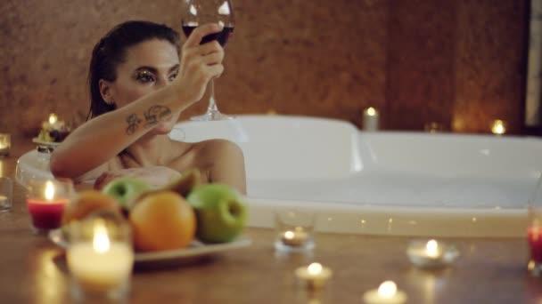 krásná žena cinkání sklenic červeného vína v lázni s přítelem