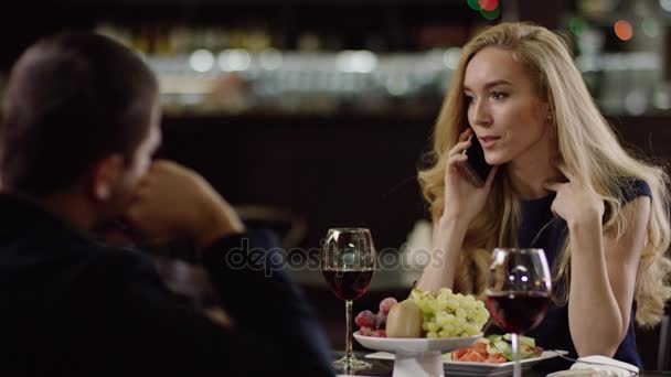 girl chatting by phone during dating in restaurant