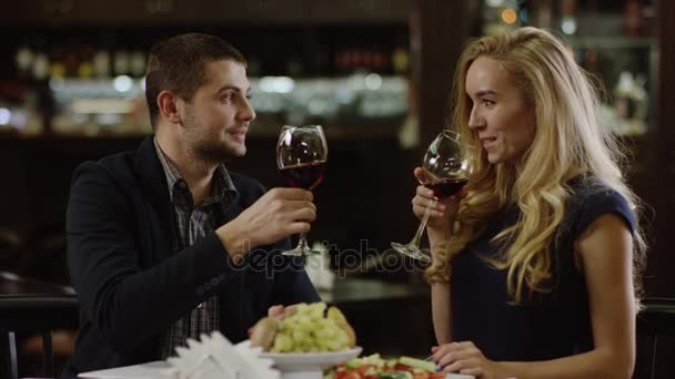 romantic couple toasting with red wine and talking