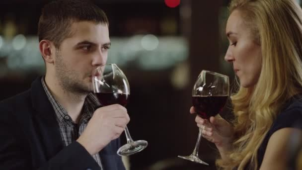 romantic couple cheering with red wine in cafe