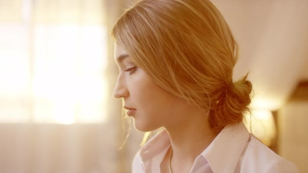 Young beautiful blonde woman turning head and looking at camera