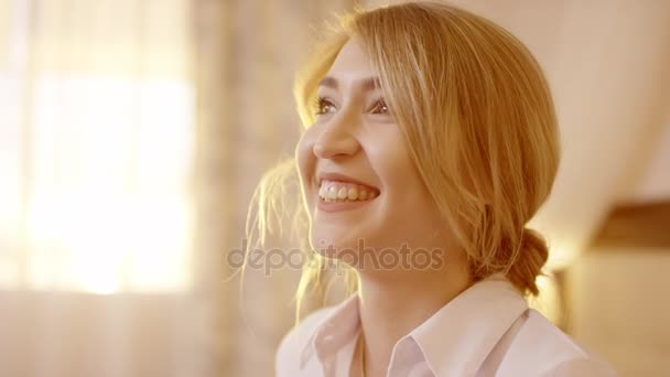 Young beautiful blonde woman smiles and laughs at the camera
