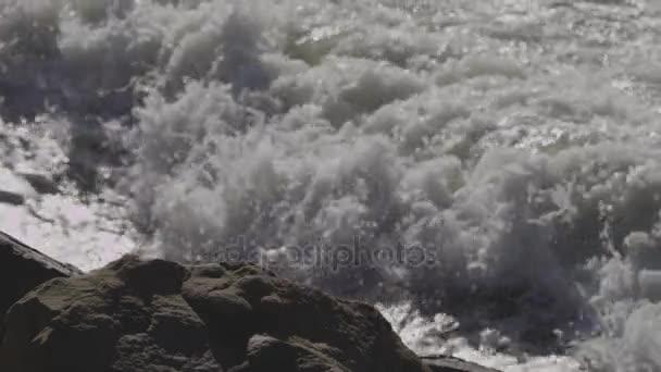Óceán hullámok összeomlik a strandon és sziklás sziklák