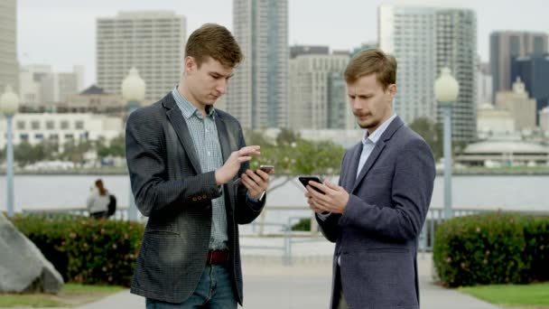 Businessmen on a street with smartphones