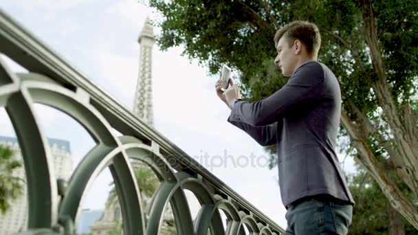 Attractive guy is taking a vacation photos by using his smartphone with the Eiffel tower on a background