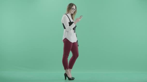 egy fiatal nő áll, kezében a telefon