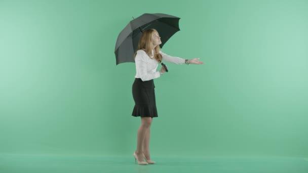 eine junge Frau steht mit einem Regenschirm