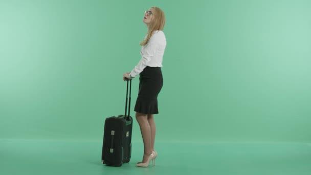 Eine blonde Frau steht mit ihrem Koffer und wartet