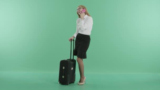 eine blonde Frau telefoniert in der Nähe eines Koffers