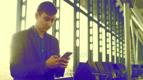Atraktivní muž používá jeho mobil pro selfie v Letiště