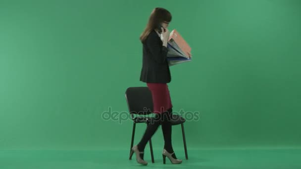Young secretary speaking on the phone sits down on the chair and starts searching through the folders she holds
