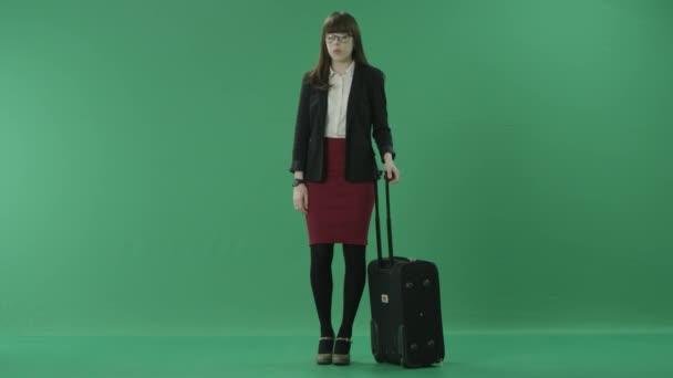 junge Geschäftsfrau steht mit ihrem Koffer und wartet auf die Abfahrt