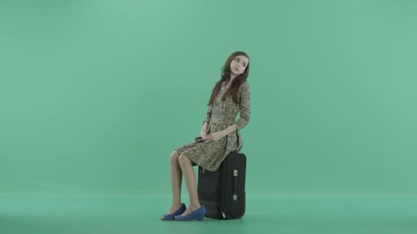 eine junge Frau sitzt auf dem schwarzen Gepäck und wartet