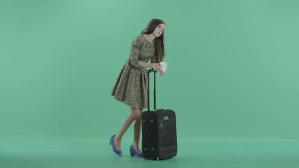 ein Mädchen steht mit ihrem Gepäck und einer Tasse in der Hand und wartet