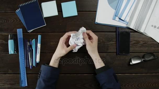 Pohled shora člověka rozvinutím zmačkaný kus papíru
