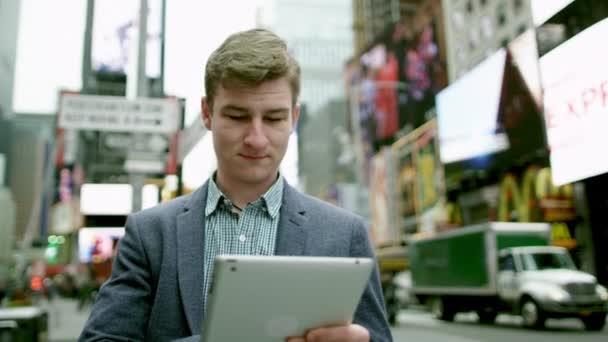 Mladý šťastný muž je SMS zpráva na svůj tablet pc na Times Square