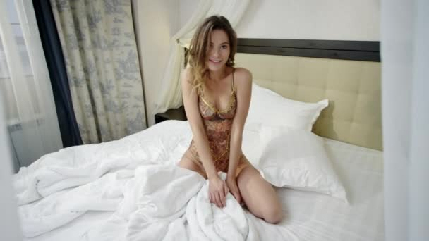 Seductive woman sitting on bed and looking to camera with passion