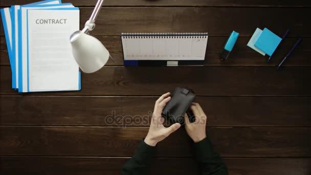 Člověk sedí v kanceláři a pomocí telefonu.