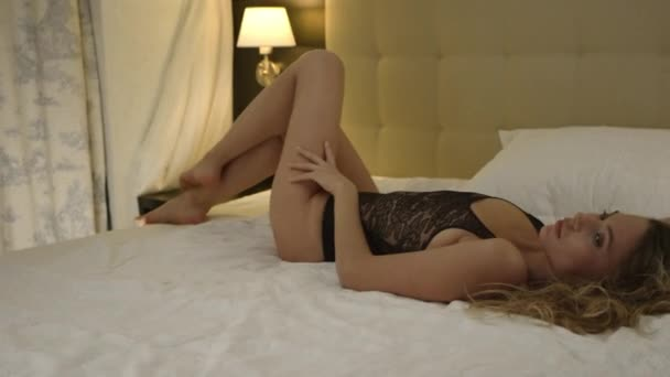Woman lies in bed and shows sexy poses in black underwear