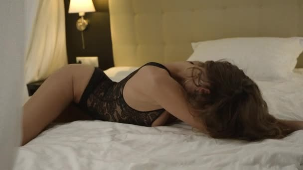 Beautiful woman lies in bed and shows sexy poses in black underwear