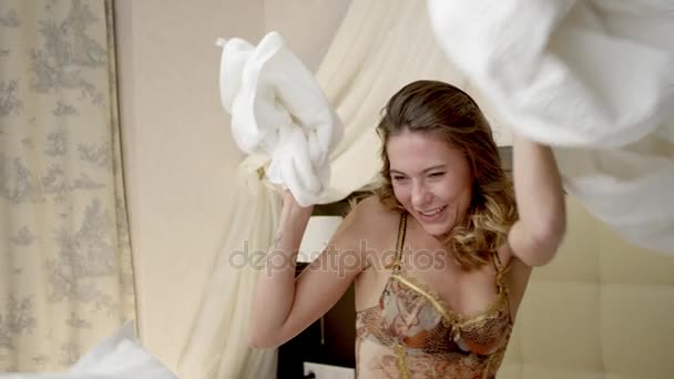 Cheerful woman having a pillow fight on bed