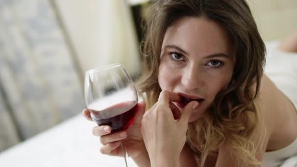 Zarte Frau trinkt Rotwein und isst Trauben im Bett
