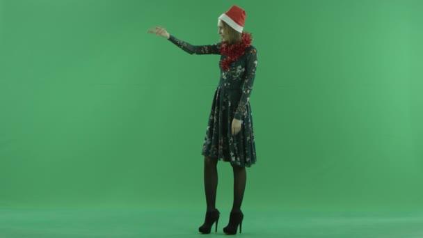 Mladá krásná žena v klobouku vánoční směřuje doleva a pozve někdo přijde, klíčování chroma na pozadí
