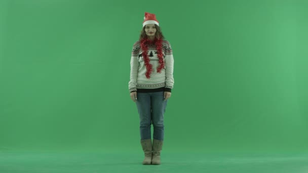 Šťastná mladá žena v klobouku Vánoce nakreslí srdce ve vzduchu, klíčování chroma na pozadí